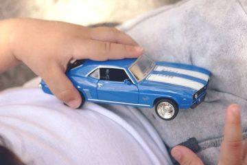 Manos de niño y coche de juguete